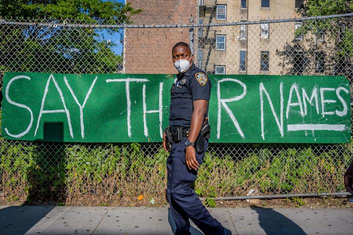 """<i>An NYPD officer walks by a banner reading """"Say Their Names"""" on June 1 in Brooklyn, New York. </i>"""
