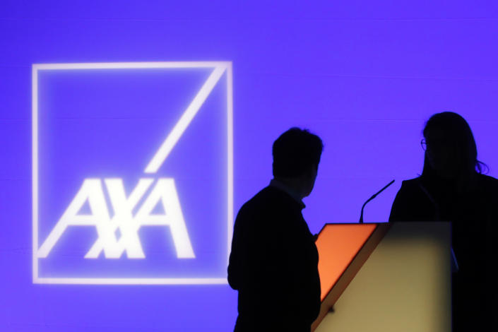 FILE - In this Feb. 21, 2019, file photo, people stand in front of the logo of AXA Group prior to the company's 2018 annual results presentation, in Paris. The Thai affiliate of Paris-based insurance company AXA said Tuesday, May 18, 2021 it is investigating a ransomware attack by Russian-speaking cybercriminals that has affected operations in Thailand, Malaysia, Hong Kong and the Philippines. (AP Photo/Thibault Camus, File)