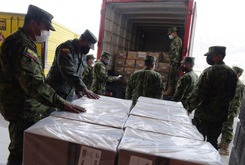 Soldiers unload boxes containing electoral material at a polling station ahead of Ecuador's presidential election on February 7, in Quito
