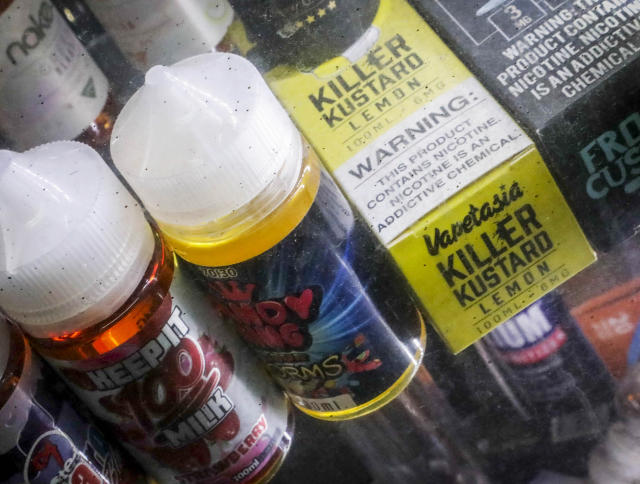 FILE- In this Sept. 16, 2019 file photo Flavored vaping solutions are shown in a window display at a vape and smoke shop in New York. Washington is joining several other states in banning the sale of flavored vaping products amid concern over the mysterious lung illness that has sickened hundreds of people and killed more than a dozen across the country. (AP Photo/Bebeto Matthews, File)