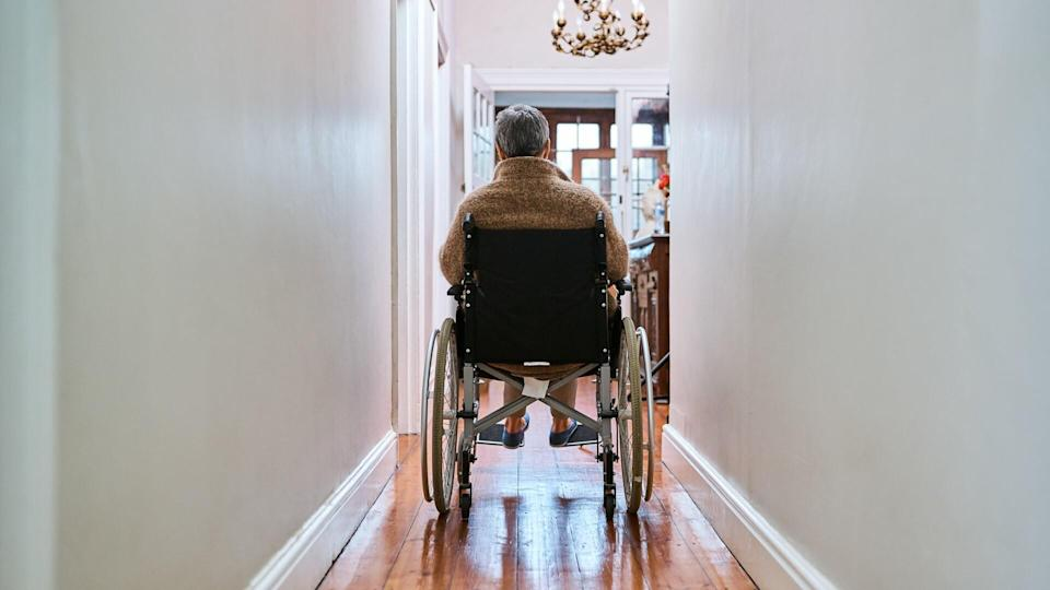 Rearview shot of a senior woman sitting in her wheelchair at home.