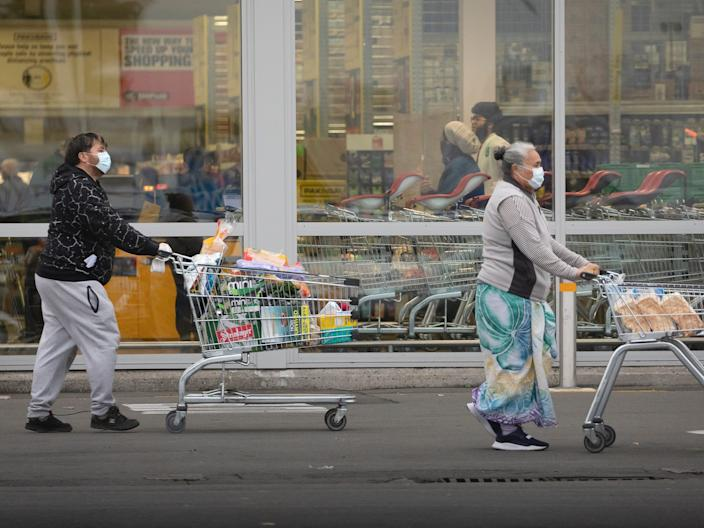 People wearing face masks, push shopping cart with their grocery items in during New Zealand's month-long, nationwide lockdown.