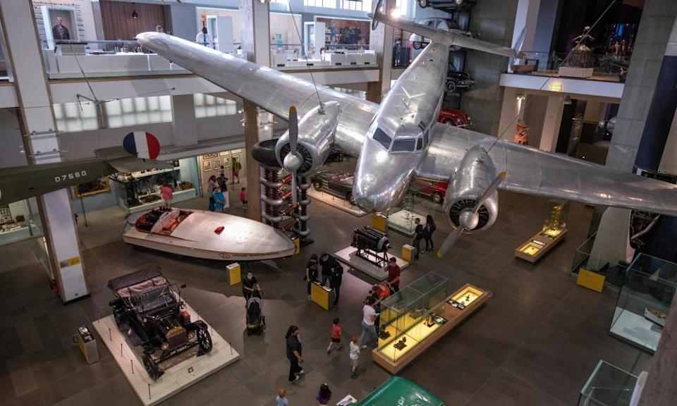 View of the Science Museum's transport display seen from above, with a vintage car and boat and a silver propeller plane suspended in mid-air from the ceiling