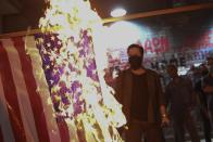 Protesters burn a US flag during a rally against the visit of the Secretary of State Mike Pompeo in Greece, outside the U.S. Consulate in the northern city of Thessaloniki, on Monday, Sept. 28, 2020. Pompeo said Monday that Washington will use its diplomatic and military influence in the region to try to ease a volatile dispute between NATO allies Greece and Turkey over energy rights in the eastern Mediterranean. (AP Photo/Giannis Papanikos)