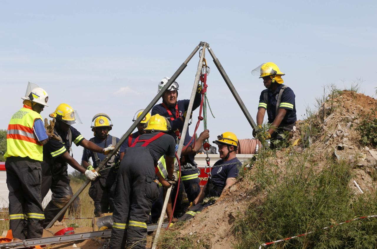 Rescue officials use hoists to remove debris as they work to rescue trapped suspected illegal miners from an abandoned gold shaft in Benoni, east of Johannesburg, February 16, 2014. South African rescuers started bringing to the surface at least 30 illegal miners on Sunday who had been trapped by debris in the abandoned gold shaft near Johannesburg, emergency services ER24 spokesman Werner Vermaak said. There were no immediate reports of deaths or injuries. Vermaak later told Reuters that some of the miners still underground were refusing to come up, saying they did not want to be arrested. REUTERS/Mike Hutchings (SOUTH AFRICA - Tags: BUSINESS COMMODITIES CRIME LAW DISASTER)