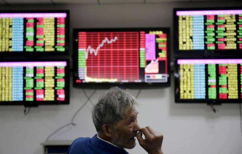 An investor looks back in front of computer screens showing stock information at a brokerage house in Wuhan