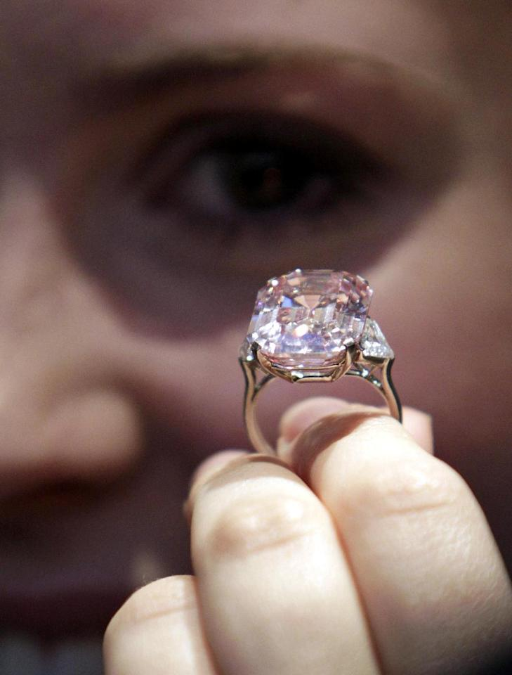 """FILE- This Oct. 25, 2010, file photo, shows an employee of Sotheby's auction house holding a 24.78 carat fancy intense pink diamond mounted as a ring, that was last seen on the market some 60 years ago according to the house, ahead of an auction in central London. In November 2010, a rare pink diamond smashed the world record for a jewel at auction, selling for more than $46 million to a well-known gem dealer. London jeweler Laurence Graff paid $46,158,674, for the 24.78-carat """"fancy intense pink"""" diamond, which he immediately named """"The Graff Pink."""" (AP Photo/Lefteris Pitarakis, File)"""