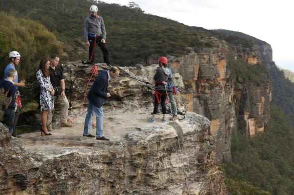 The Duke of Cambridge (centre) looks over the edge of a cliff as he and the Duchess of Cambridge visit the Narrow Neck Lookout and observes abseiling by the Mountain Youth Services group in the Blue Mountains town of Katoomba, west of Sydney. PRESS ASSOCIATION Photo. Picture date: Thursday April 17, 2014. See PA story ROYAL Tour. Photo credit should read: Phil Noble/PA Wire
