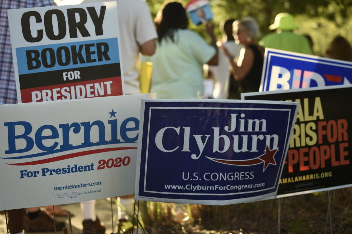 "Supporters of many of the Democrats seeking their party's presidential nomination plant signs outside the venue for Majority Whip Jim Clyburn's ""World Famous Fish Fry"" on Friday, June 21, 2019, in Columbia, S.C. (AP Photo/Meg Kinnard)"