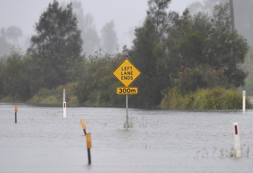 A road sign is surrounded by flood water at Tumbulgum, NSW on December 14. Source: AAP