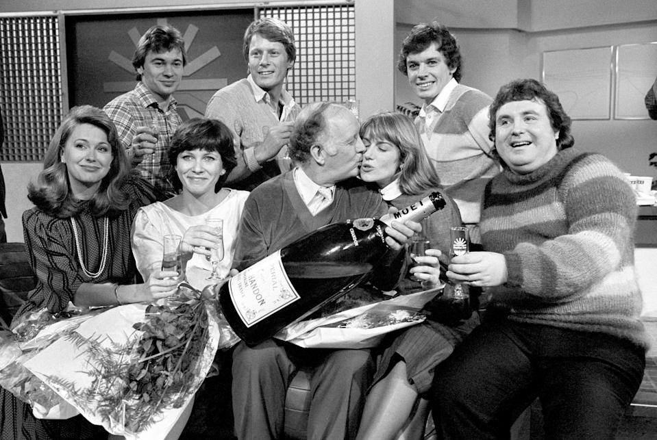 JANUARY 17TH : On this day in 1983 early morning breakfast television began with BBC's 'Breakfast Time'. BBC-TV launched their first Breakfast Time programme at 6:30 and at the closing stages gathered in the studio for a champagne and cake celebration. Left to right: Back row: Weatherman Francis Wilson, Nick Ross and David Icke. Front row: Jane Pauley, an American who runs her own breakfast show, Debbie Rix, Frank Bough kissing Selina Scott and astrologer Russell Grant. (Photo by PA Images via Getty Images)