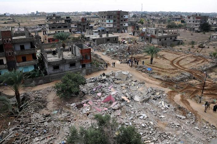 Residents gather next to the remains of buildings destroyed by the Egyptian military in divided border town of Rafah, along the border with the Hamas-run Gaza Strip, on November 4, 2014 (AFP Photo/Mohamed el-Sherbeny)