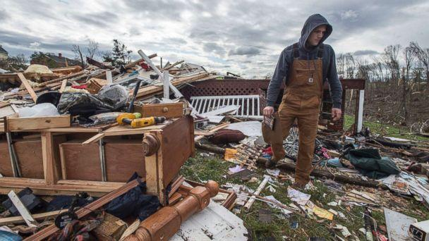 PHOTO: Ryan Polaski sorts through debris of his father-in-law's house after severe weather, April 16, 2018 in Elon, Va. (Jay Westcott/AP)