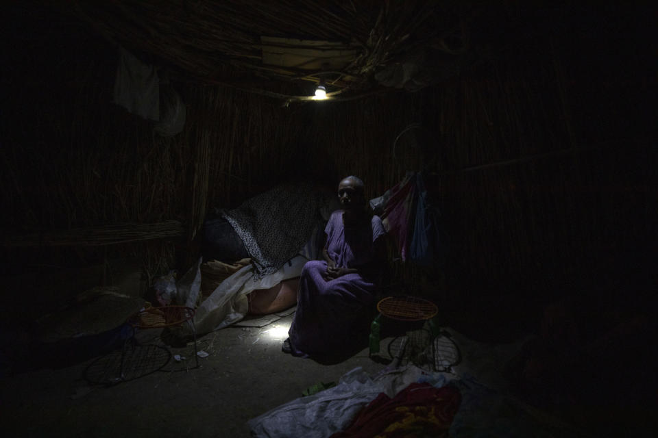 """Tigrayan refugee Belaynesh Beyene, 58, who fled the conflict in the Ethiopia's Tigray, sits in her shelter in Hamdayet, eastern Sudan, near the border with Ethiopia, on March 13, 2021. Beyene said she saw 24 bodies in Dansha. """"They accidentally killed an ethnic Oromo in a Tigrayan household,"""" she said. """"When they realized their 'mistake,' they came and buried him."""" (AP Photo/Nariman El-Mofty)"""