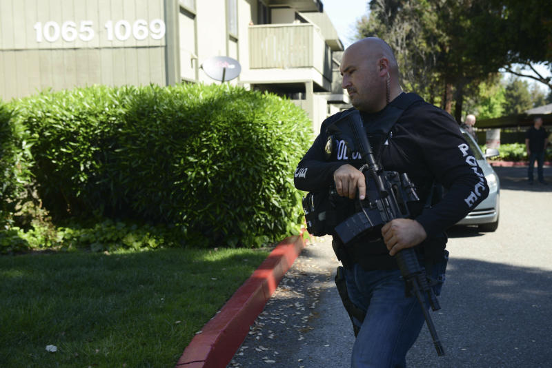 Police approach the apartment complex believed to be associated with a car crash suspect in Sunnyvale, Calif., on Wednesday, April 24, 2019. Investigators are working to determine the cause of a crash in Northern California that injured eight pedestrians on Tuesday evening. Authorities say the driver of a car was taken into custody after he appeared to deliberately plow into them. (AP Photo/Cody Glenn)