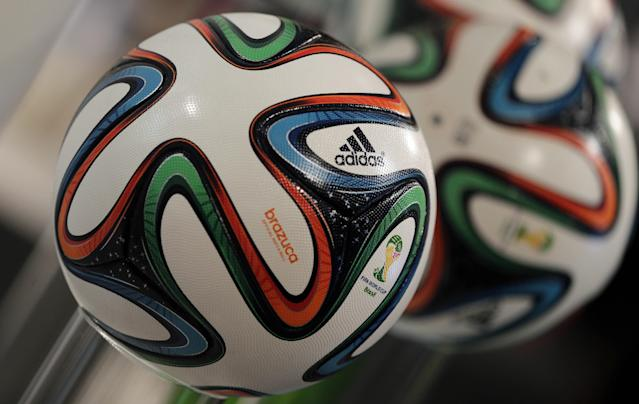 FILE - This May 8, 2014 file photo shows the adidas logo printed on the official FIFA World Cup 2014 soccer ball in Fuerth, Germany. The competition on the pitch in has yet to start, but the fight over World Cup consumers is already intense _ and no more so than between the athletic companies that are jockeying for their once-every-four-years shot at the ever-growing soccer market. (AP Photo/Matthias Schrader, File)