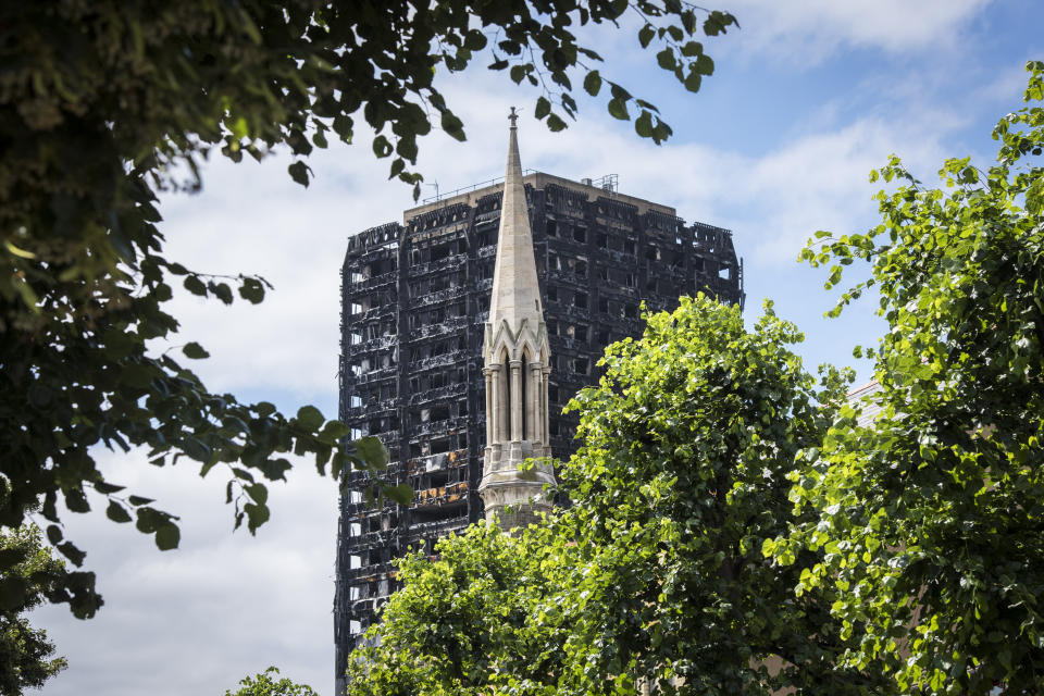 General view of the remains of the Grenfell Tower, with the tower of Notting Hill Methodist Church, a month after fire engulfed the 24-storey block in Kensington, London. Picture date: Wednesday July 12th, 2017. Photo credit should read: Matt Crossick/ EMPICS Entertainment.