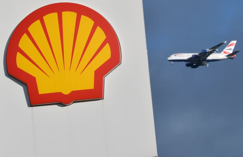 A passenger plane flies behind a Shell logo at a petrol station in west London