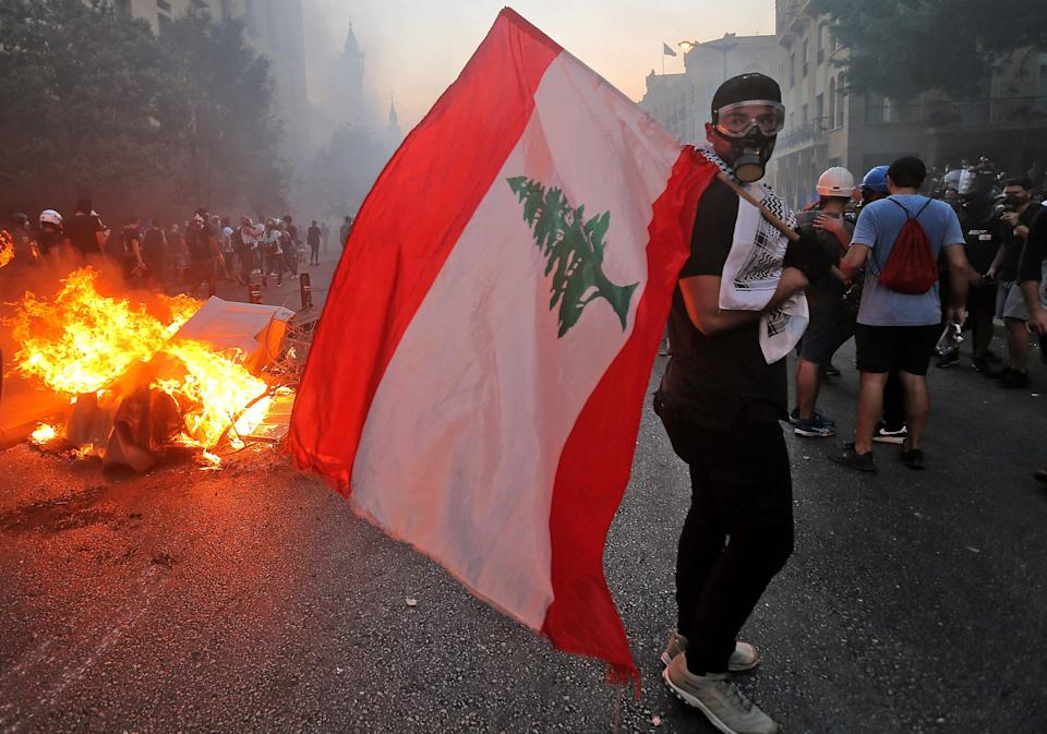 A protester stands with a Lebanese national flag during clashes with army and security forces near the Lebanese parliament (AFP/Getty)