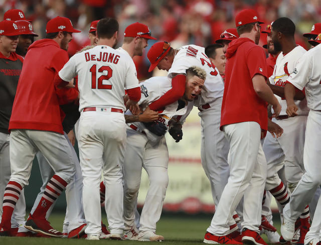 St. Louis Cardinals catcher Yadier Molina, center, is mobbed by teammates after hitting a winning sacrifice fly to score Kolten Wong and defeat the Atlanta Braves in the 10th inning of Game 4 of a baseball National League Division Series, Monday, Oct. 7, 2019, in St. Louis. (Curtis Compton/Atlanta Journal-Constitution via AP)