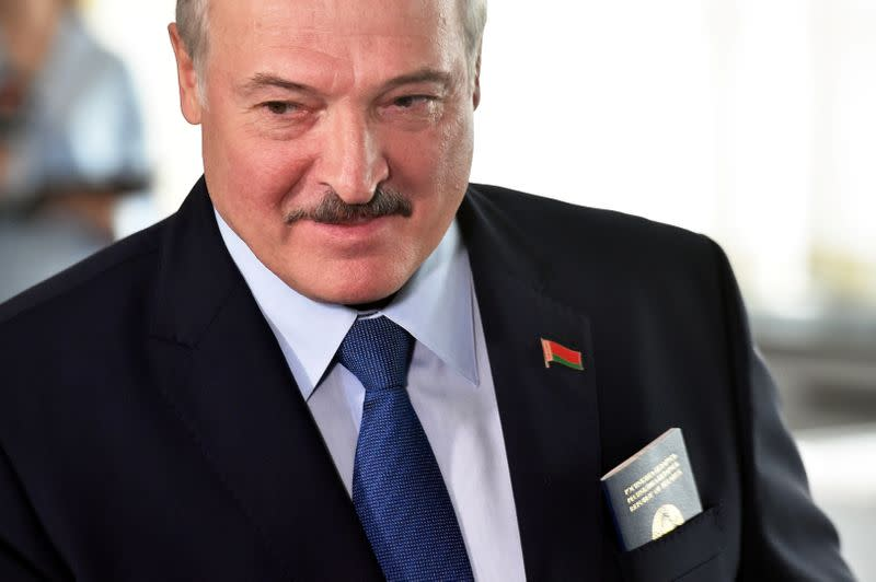 Belarusian President Alexander Lukashenko visits a polling station during the presidential election in Minsk