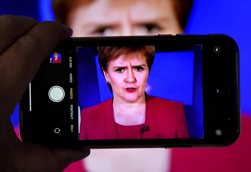 A person uses their phone to film a televised broadcast of First Minister Nicola Sturgeon (Andrew Milligan/PA) (PA Wire)