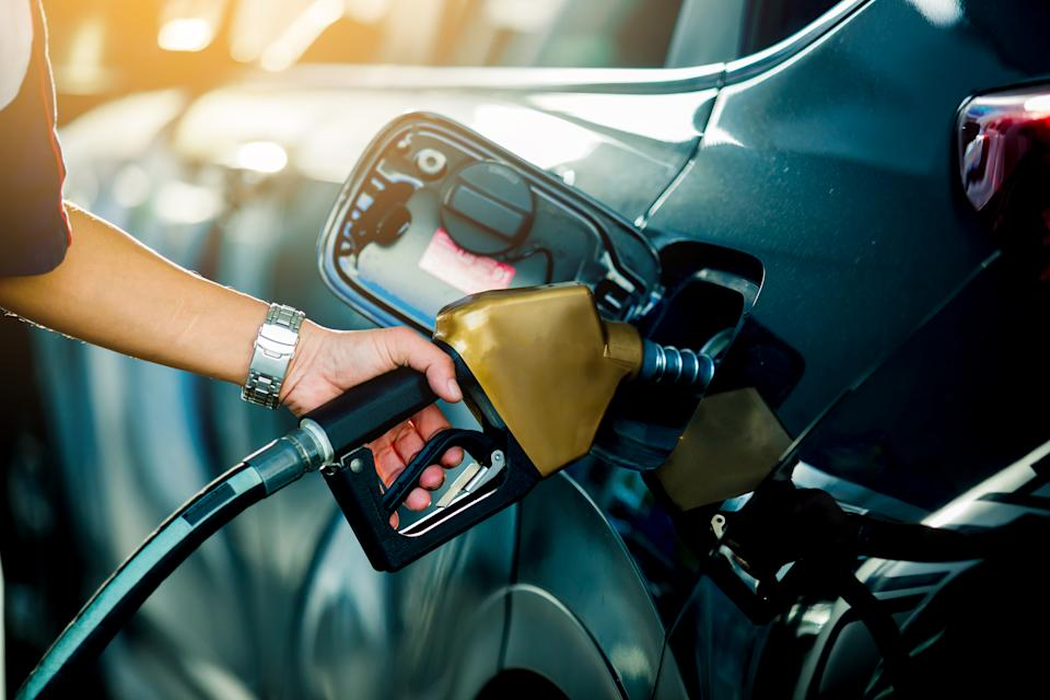 Hand refilling the car with fuel at the refuel station, the concept of fuel energy