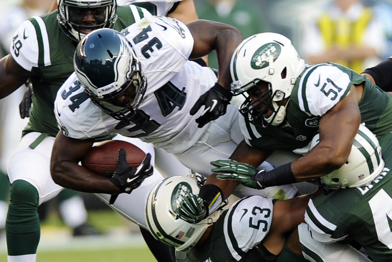 Philadelphia Eagles running back Bryce Brown (34) is tackled by New York Jets linebacker Josh Mauga (53) cornerback D'Anton Lynn (41) and linebacker Aaron Maybin (51) as linebacker Demarlo Davis (49) watches in the first half of a preseason NFL football game, Thursday, Aug. 30, 2012, in Philadelphia. (AP Photo/Michael Perez)