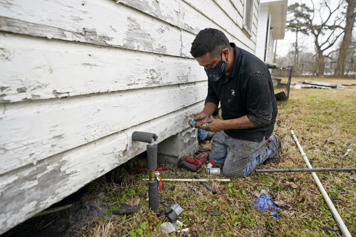West Street Recovery's Johnny Vicar works to repair busted pipes under a home, that were frozen during the recent winter storm, Thursday, Feb. 25, 2021, in Houston. West Street Recovery, a nonprofit created in the wake of Hurricane Harvey to help repair flood damaged homes, has been working since the winter storm hit to repair and replace damaged plumbing systems for residents who can't afford to do so. (AP Photo/David J. Phillip)