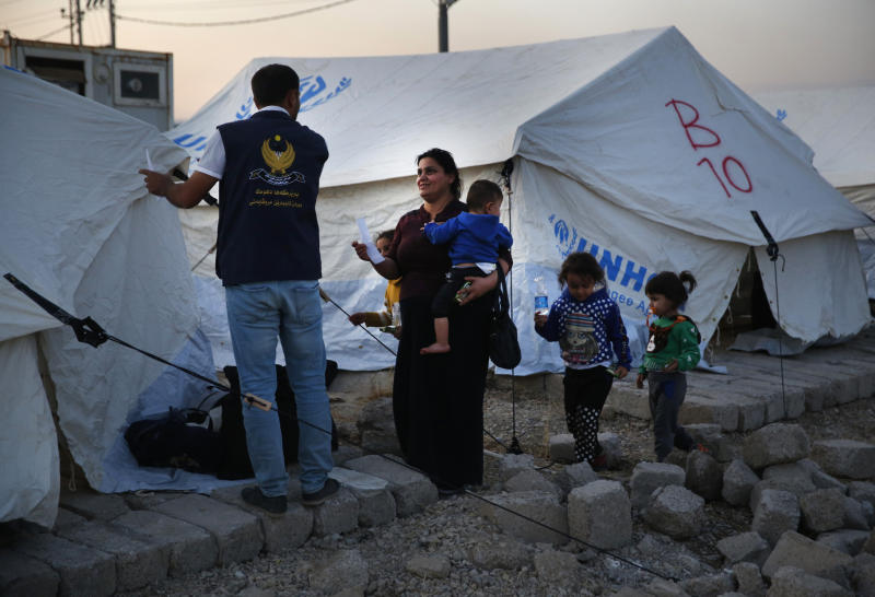 A Syrian woman with her children, who are newly displaced by the Turkish military operation in northeastern Syria, receives a tent from a Kurdish humanitarian worker upon her arrival at the Bardarash camp, north of Mosul, Iraq, Wednesday, Oct. 16, 2019. The camp used to host Iraqis displaced from Mosul during the fight against the Islamic State group and was closed two years ago. The U.N. says more around 160,000 Syrians have been displaced since the Turkish operation started last week, most of them internally in Syria. (AP Photo/Hussein Malla)