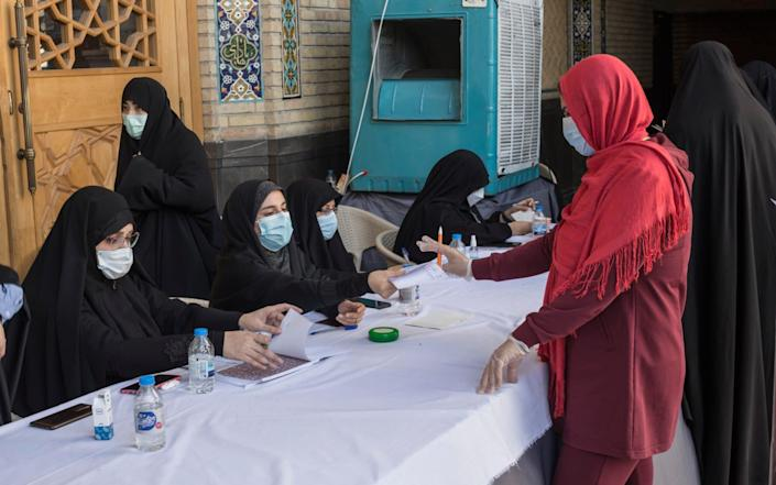 A woman collects her ballot to vote in the presidential electin at a polling station set up in a mosque in Tehran. - Sam Tarling/Sam Tarling for The Telegraph
