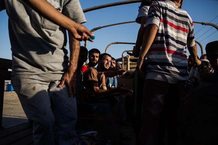 <p>A group of refugees from Mosul after being checked by the Intelligence Officers in Haman Al-Alil on their way to the refugee camps. Haman Al-Alil, Iraq. June 29, 2017. (Photograph by Diego Ibarra Sánchez / MeMo) </p>
