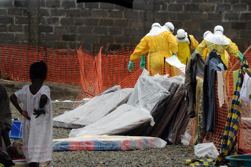 Health care workers wearing full body suits carry a body at the Elwa hospital in Monrovia on August 30, 2014