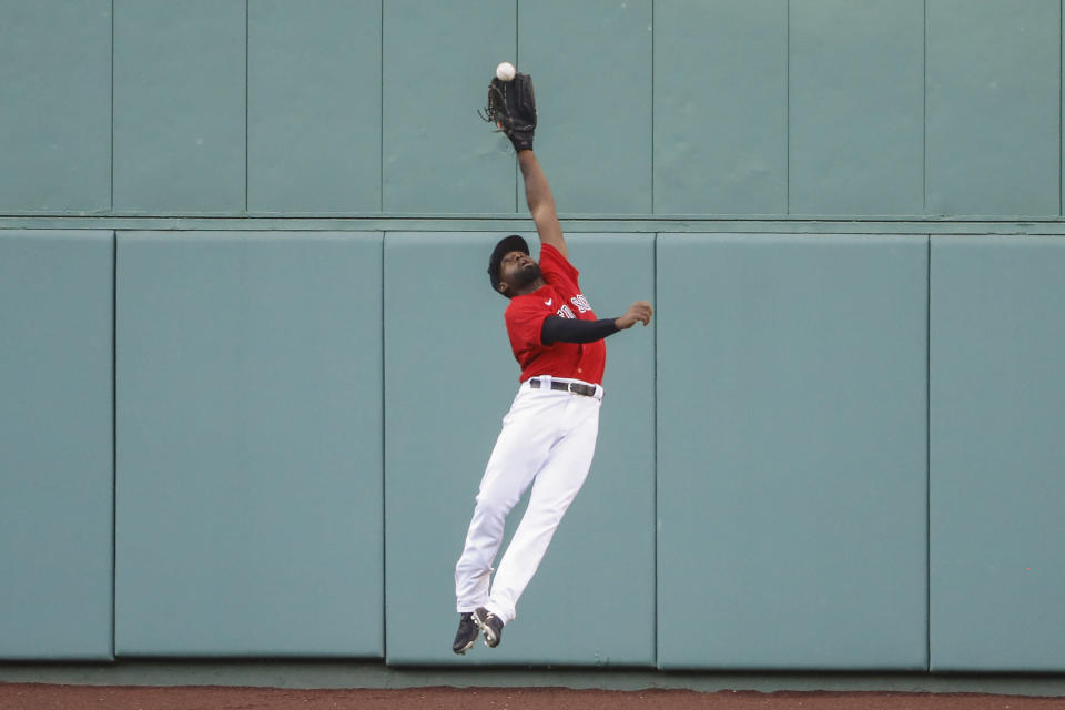 FILE - Boston Red Sox center fielder Jackie Bradley Jr. makes a leaping catch on a ball hit by Toronto Blue Jays' Rowdy Tellez during the sixth inning of the first baseball game of a doubleheader at Fenway Park in Boston, in this Friday, Sept. 4, 2020, file photo. Free-agent outfielder Jackie Bradley Jr. is joining the Milwaukee Brewers, agreeing to the parameters of a $24 million, two-year contract, a person familiar with the negotiations told The Associated Press. The person spoke on condition of anonymity Thursday, March 4, 2021, because the details of the agreement were still being negotiated and the deal is subject to a successful physical.(AP Photo/Winslow Townson, File)