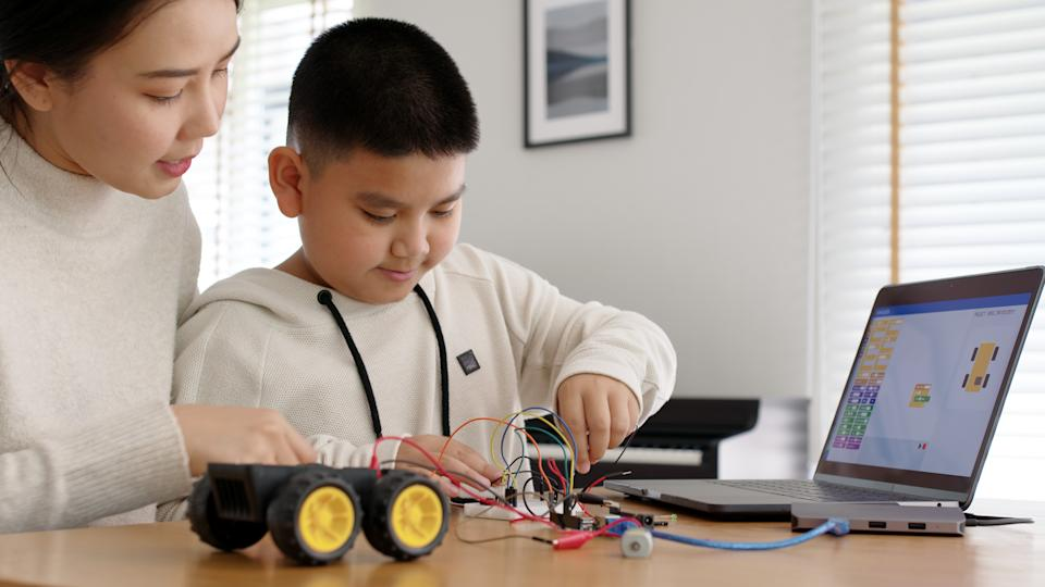 Young asia student remotely learn online at home with parent in coding robot car and electronic board cable in STEM, STEAM, mathematics engineer science technology computer code in robotics for kids.