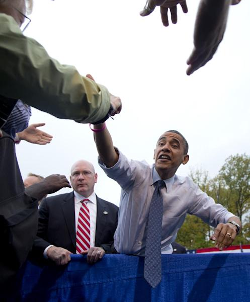 President Barack Obama stretches to shakes hands with supporters after speaking about the choice facing women in the upcoming election, Friday, Oct. 19, 2012, at a campaign event at George Mason University, in Fairfax, Va. (AP Photo/Carolyn Kaster)