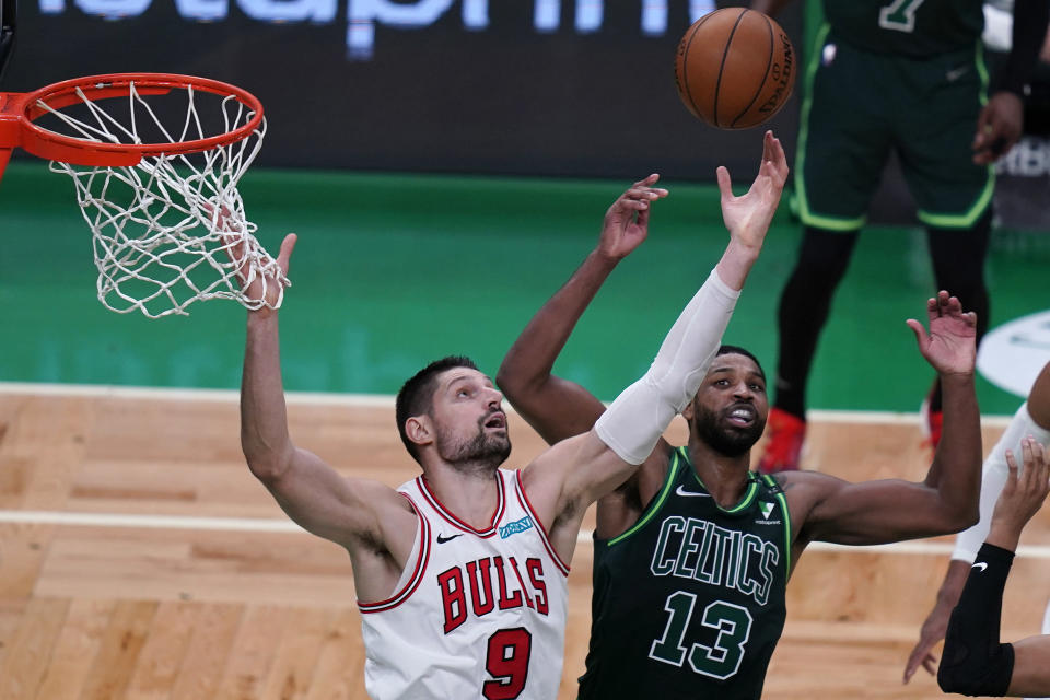 Chicago Bulls center Nikola Vucevic (9) reaches for a rebound against Boston Celtics center Tristan Thompson (13) during the second half of an NBA basketball game, Monday, April 19, 2021, in Boston. (AP Photo/Charles Krupa)