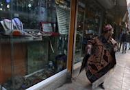 A local vendor carries a carpet for sale on Chicken Street in Kabul, on December 7, 2014 (AFP Photo/Wakil Kohsar)