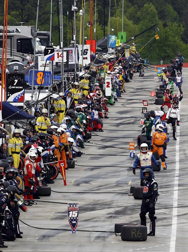 Pit crews wait for their drivers on pit road during the Indy Grand Prix of Alabama auto race on Sunday, April 27, 2014, in Birmingham, Ala. (AP Photo/Butch Dill)
