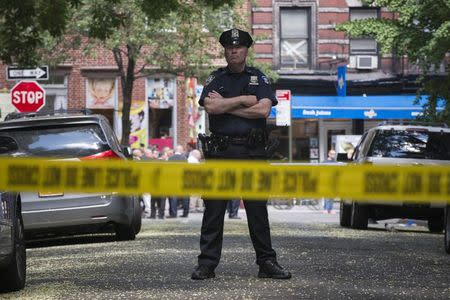 A New York Police Officer stands guard inside a cordoned area at the site of a shooting in Greenwich Village, Manhattan, New York
