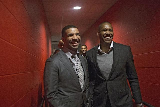 Hip Hop Star Drake, left, chats with Toronto Raptors general manager Masai Ujiri following a press conference before the Toronto Raptors' NBA game against the Brooklyn Nets in Toronto on Saturday January 11, 2014. (AP Photo/The Canadian Press, Chris Young)