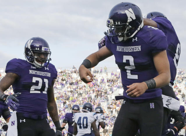 Northwestern quarterback Kain Colter (2) celebrates with running back Stephen Buckley (8) after scoring a touchdown as wide receiver Kyle Prater (21) looks on during the second half of an NCAA college football game against Maine in Evanston, Ill., Saturday, Sept. 21, 2013. Northwestern won 35-21. (AP Photo/Nam Y. Huh)