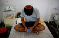An Indian Jew, member of the Bnei Menashe, suffering from the coronavirus disease, checks his mobile phone as he sits on a bed at a COVID-19 care facility inside a Gurudwara or a Sikh Temple, in New Delhi