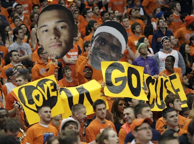 Syracuse fans cheer while waving cutouts of Syracuse players Tyler Ennis, left, and C.J. Fair, right, in the second half of an NCAA college basketball game against Pittsburgh in Syracuse, N.Y., Saturday, Jan. 18, 2014. Syracuse won 59-54. (AP Photo/Nick Lisi)