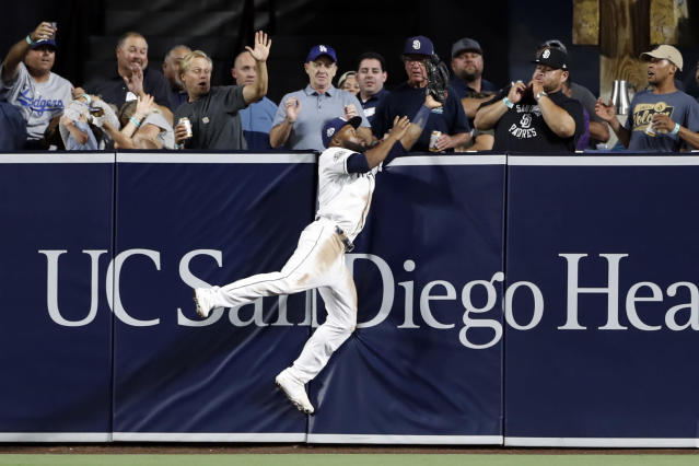 San Diego Padres center fielder Manuel Margot makes the catch at the wall for the out on Los Angeles Dodgers' Cody Bellinger during the sixth inning of a baseball game Tuesday, Aug. 27, 2019, in San Diego. (AP Photo/Gregory Bull)