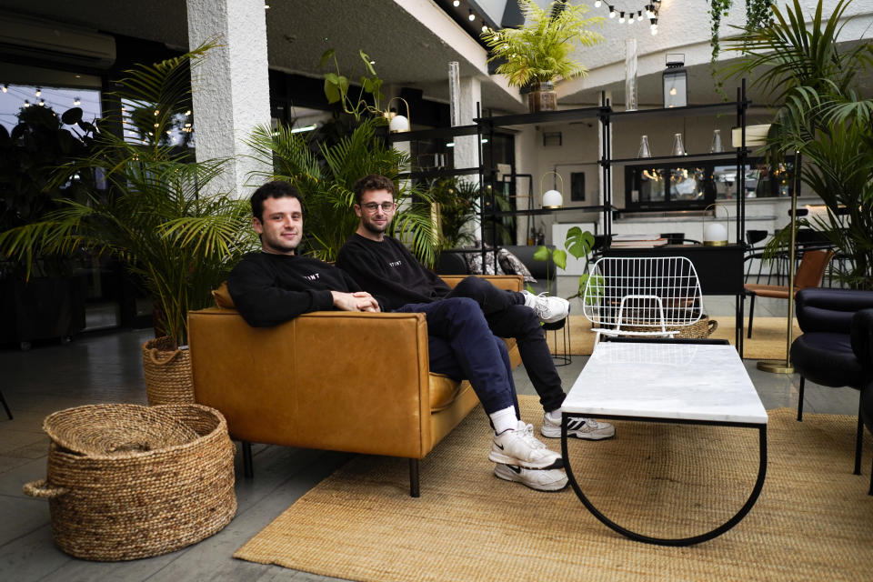 Co-founders of the app Stint, brothers Sam, left, and Sol Schlagman, sit on a couch, at their headquarters in Camden, London, Monday, Aug. 23, 2021. With Britain facing a pandemic and Brexit-induced labor shortage, some apps that recruit gig workers are playing a role in alleviating this shortage, such as Stint. In the U.S., similar apps addressing the pandemic-induced labor shortage are Gig Pro and Instaworks.(AP Photo/Alberto Pezzali)
