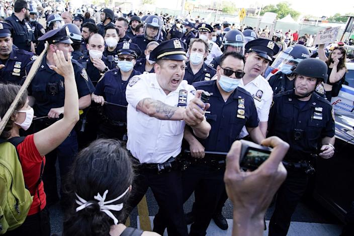 An NYPD police officer sprays protesters as they clash during a march in Brooklyn, New York, May 30.