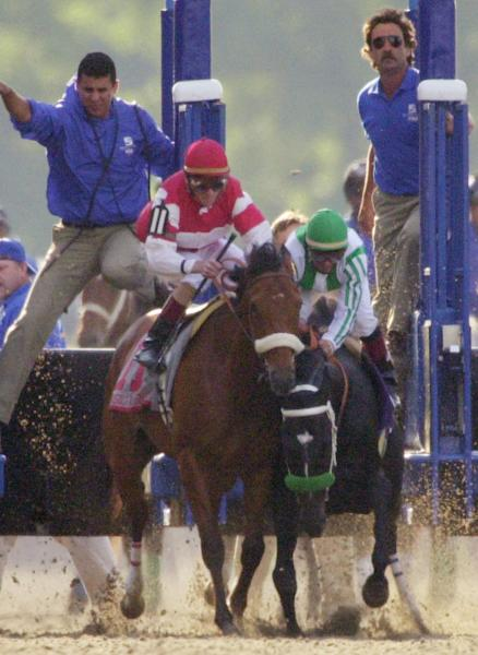 FILE - In this June 8, 2002, file photo, War Emblem, right, ridden by Victor Espinoza, stumbles into Magic Weisner, ridden by Richard Migliore, as he leaves the gate during the Belmont Stakes horse race in Elmont, N.Y. The race was won by Sarava, ridden by Edgar Prado, ending War Emblem's shot at the Triple Crown. (AP Photo/Dave Martin, File)