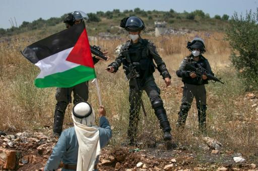 A Palestinian man facing Israeli forces waves a national flag during a protest against Israel's plan to annex parts of the occupied West Bank, near the town of Tulkarm on June 5