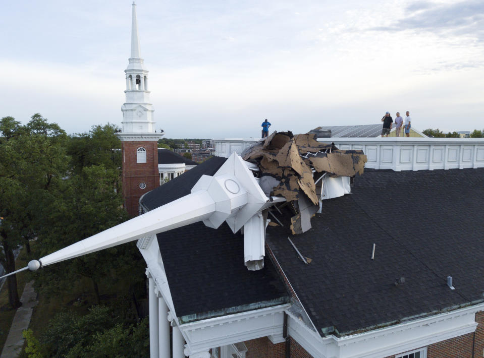 The steeple at College Church in Wheaton, Ill. was toppled during a storm Monday, Aug. 10, 2020, in the northwest suburbs of Chicago, Ill. Church officials check out the damage from the rooftop which also left several trees in the nearby park heavily damaged. (Mark Welsh /Daily Herald via AP)